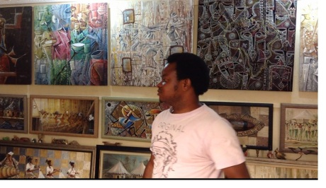 One of Gbolade`s many students avidly explaining the difference in styles between the variety of paintings.
